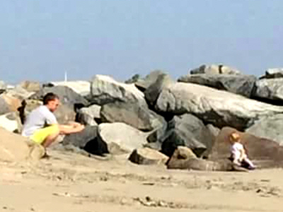 Man sits his child on top of a stranded, sick sea lion in California