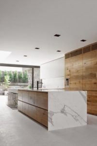kitchen-with-unfinished-wood-cabinets-and-marble-waterfall-kitchen-island-counter