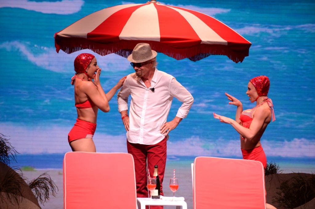 Richard Branson on stage for the announcement with two women in red swimsuits & caps, a red & white striped umbrella, and 2 red deck chairs with an ocean backdrop