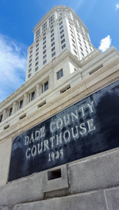 Low angle photo of the historic Dade County Courthouse, built in 1925. Photo shows the black granite sign embedded in the wall & the tower against the blue sky
